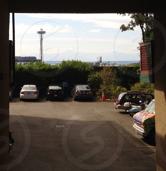 cars parked near green leaf plants and Space Needle during daytime photo