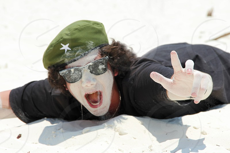 A young guy in sunglasses is lying on a white sandy beach and fooling around smearing his face in the sand and shouting joyfully. The concept of happiness relaxation no problem everything is fine. photo