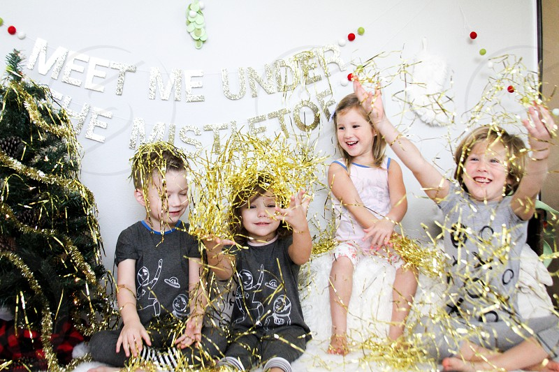 three girls and boy sitting on white cushion near christmas tree and wall photo