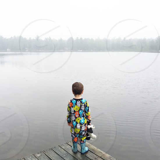 boy in blue black yellow green sweater standing on wooden pier facing misty lake photo