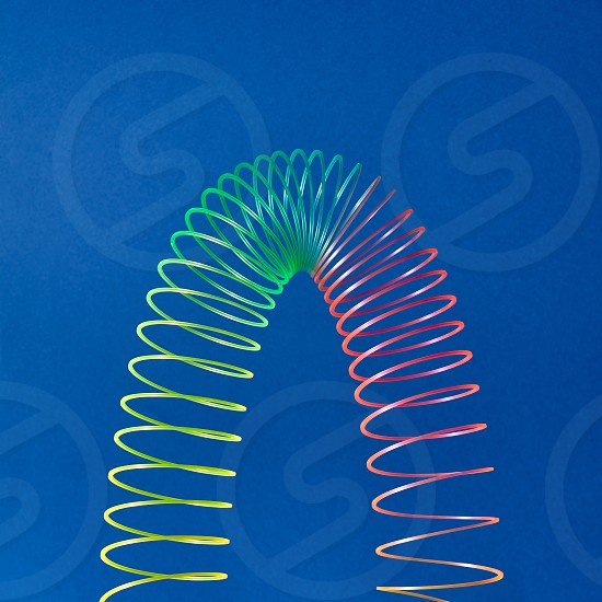 Stratching colorful toy spiral in the shape of parabola on a blue background with copy space. photo