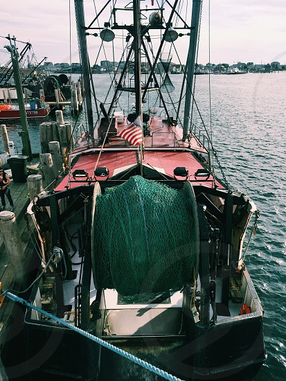 black red and white trawler moored in dock photo