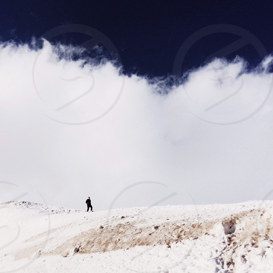 man on top of snow covered mountain photo