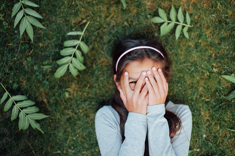 young little girl crying on the grass. Portrait face eyes hands summer time photo