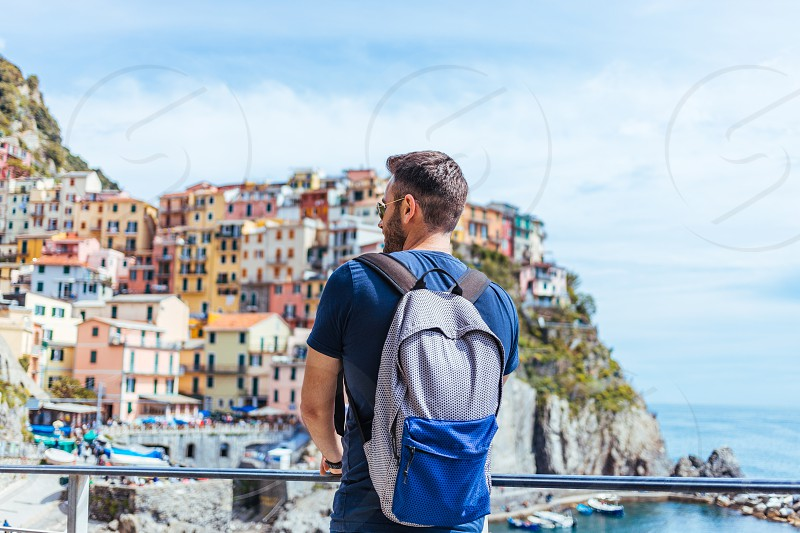 Young man enjoying the view of Manarola in the UNESCO World Heritage Site Cinque Terre Liguria Italy photo