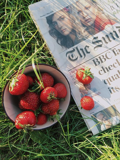white and gray bowl full of strawberries next to a newspaper photo