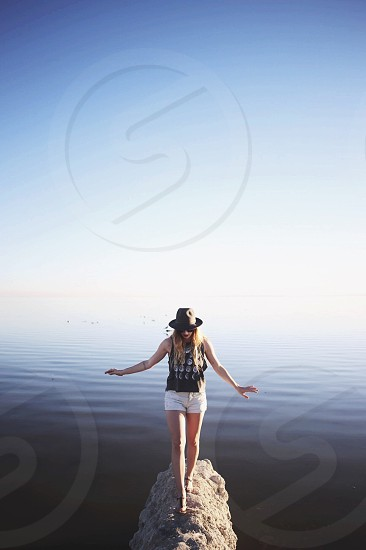 woman in black tank top carefully walking rock over the water during daytime photo