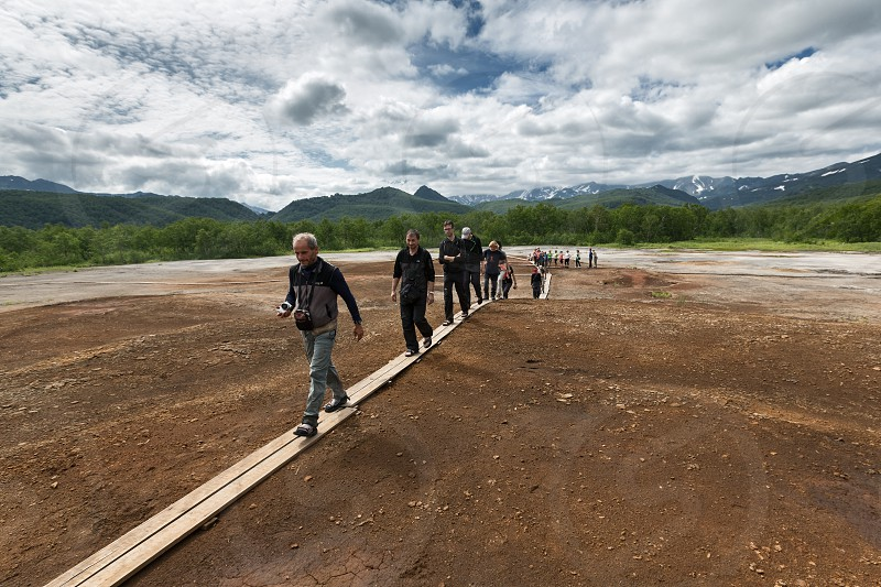 NALYCHEVO KAMCHATKA RUSSIA - JULY 30 2014: Tourists walk on wooden deck overlooking Thermal Pad Boiler or Travertine Shield Boiler with sleep and active griffins (mud pot) with thermal water. photo