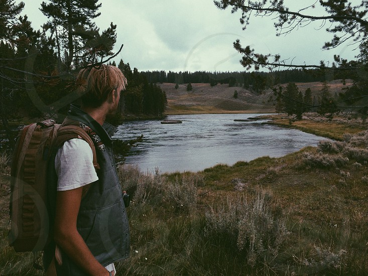 river with man wearing brown backpack and white short sleeve shirt photo