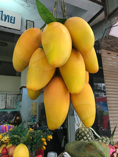 Outdoor day colour vertical portrait Thailand Thai Kingdom Asia Asian East Eastern Orient culture temple travel wanderlust tourist tourism shop store Grocer grocery groceries fruit mango mangoes bright vivid vibrant colourful yellow fresh ripe hanging food ingredients photo