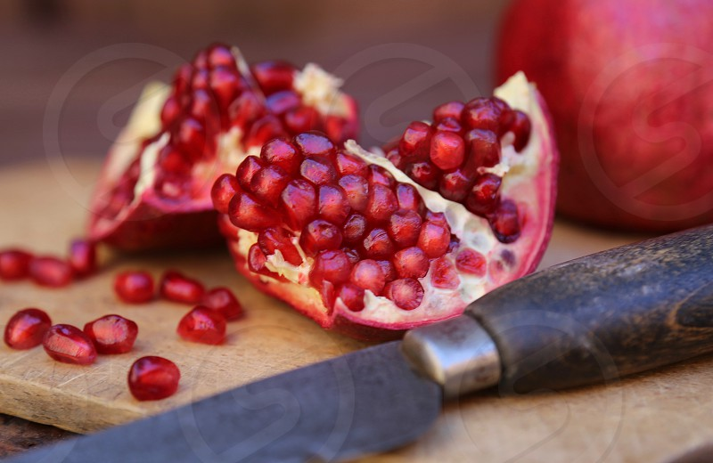 Pomegranates on Cutting Board with Knife photo