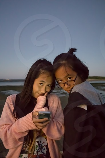 two Asian teenage girls at sunset hours at beach making funny face and using smartphone photo