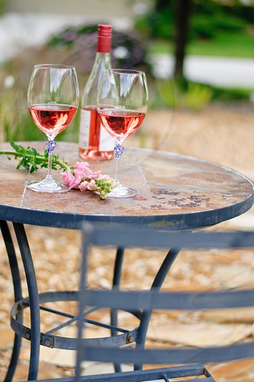 two wine glasses and bottle on patio table photo