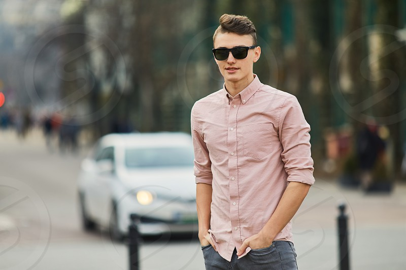Young boy walking on the city street wear glasses and smile to the camera photo