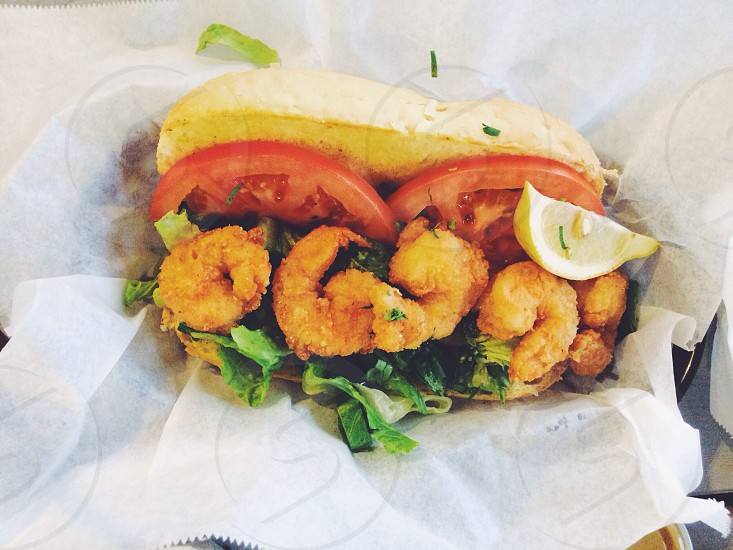 Fried shrimp po'boy on a hoagie roll with lettuce tomato and a slice of lemon. Fresh vibrant health food served picnic style. A delicious dinner!  photo
