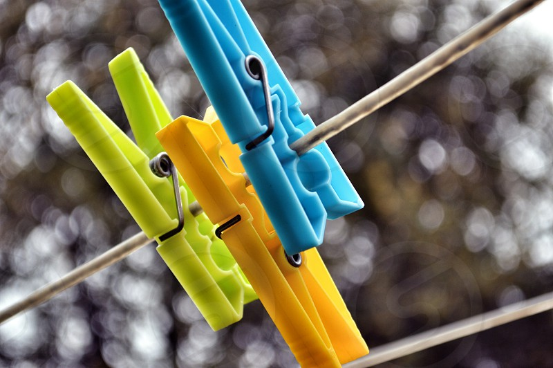 close up photo of blue orange and green clothes clips photo