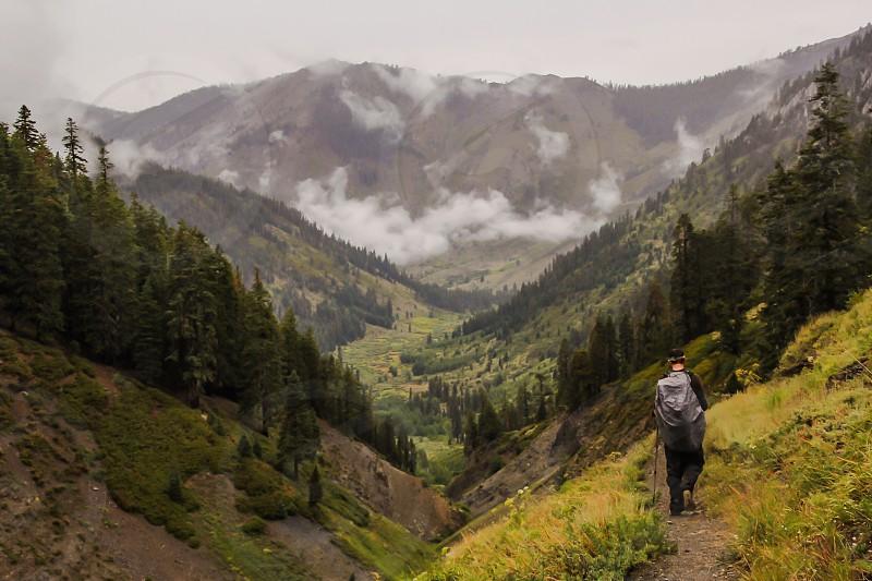 man walking down the mountain path photo