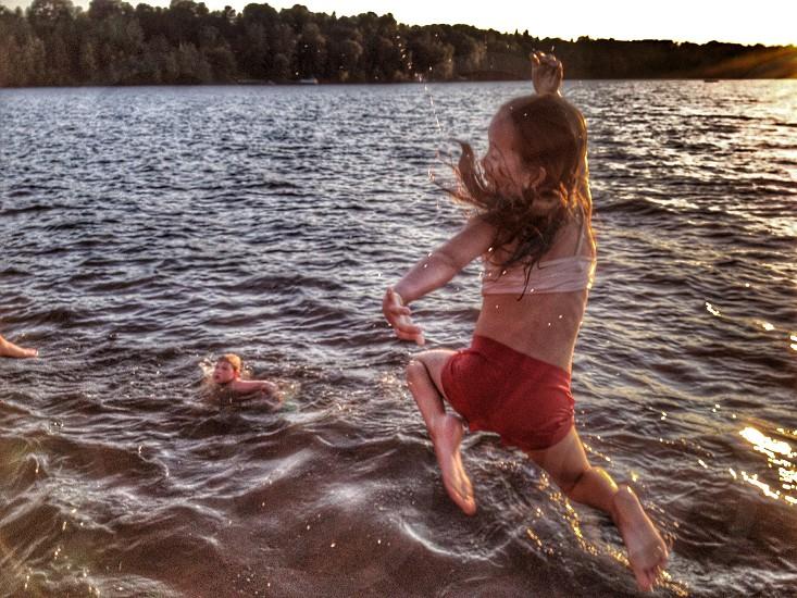 Child jumping into lake at sunset photo