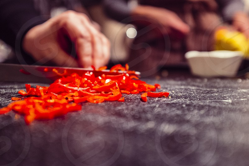 man slicing red bell pepper photo