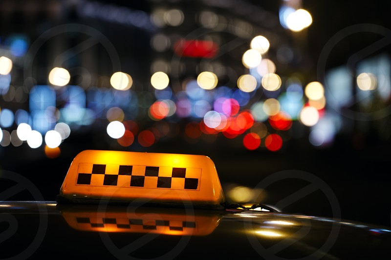 lluminated traditional yellow taxi sign on top of a cab in a city street with a colourful bokeh of urban lights photo