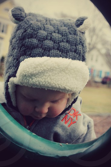 Toddler in winter wear playing on playground. photo