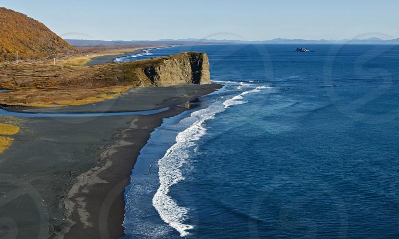 Panoramic view of Pacific Coast with black volcanic sand on the beach. Beautiful autumn landscape: Khalaktyrsky Beach on Kamchatka Peninsula (Russia Far East). photo