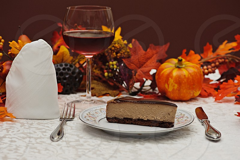 Food Photography - Slice of Chocolate Cheesecake in a fall arrangement with glass of wine. photo