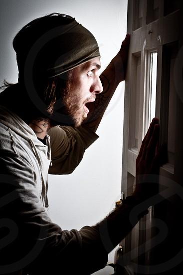Man peering through lit window in door photo