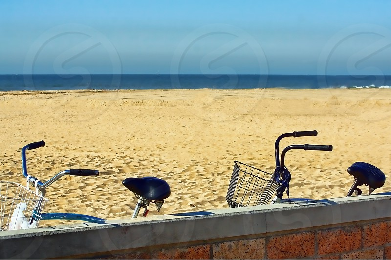 A pair of bicycles lean against a wall on an empty sandy beach near the ocean photo