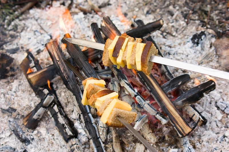 Cheese and bread roasted on the fire on the metal sticks photo