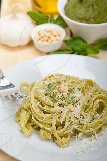 Italian traditional basil pesto pasta ingredients parmesan cheese pine nuts extra virgin olive oil garlic on a rustic table  photo