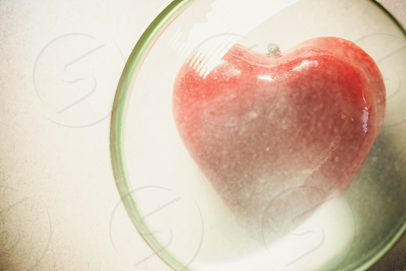 Symbolically showed examination of a heart souvenir in shape of heart viewed through magnifier.  photo