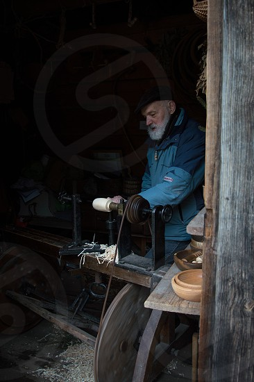 Carpenter portrait. Woodworker at his lathe doing wood work photo