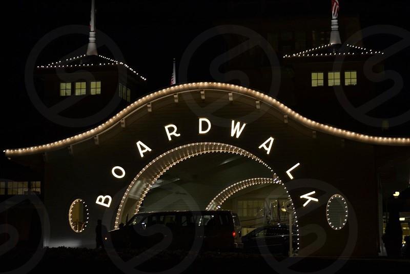lit boardwalk sign at night photo