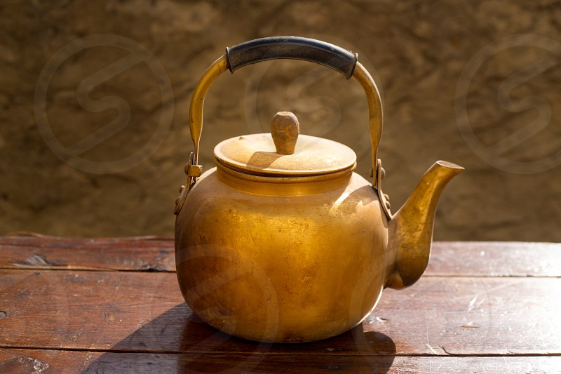 Antique brass teapot on vintage wooden aged table photo