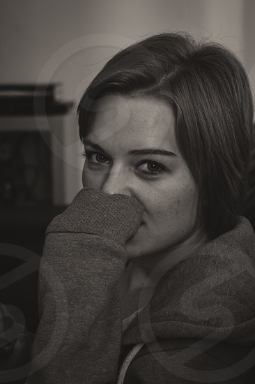 woman in pull-over hoodie covering her face with left hand grayscale photo photo