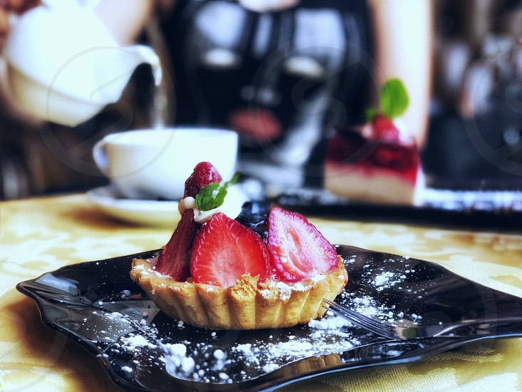 Tartlet with fresh strawberries and berries on a beautiful black plate on a table in a cafe. In the background a girl pours tea from a teapot. photo