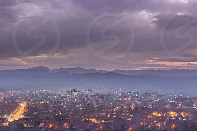Misty night view of Pirot cityscape and dramatic blue hour sky photo