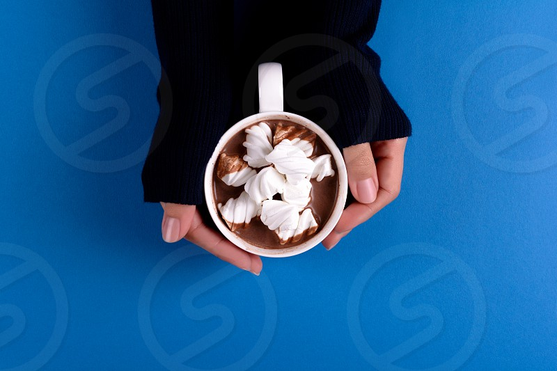 Feminine hands holding hot chocolate with marsmallow candies on blue paper background. Top view. Copy space. photo