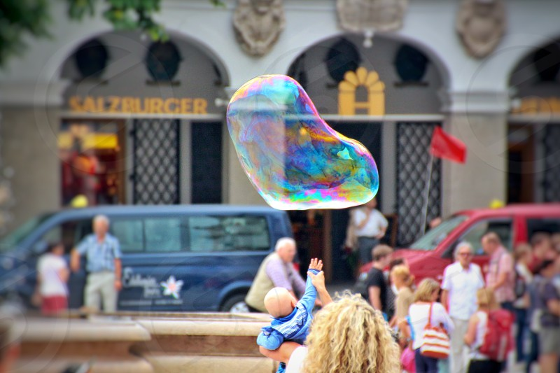 Baby reaching for a large bubble in a public square in Germany photo