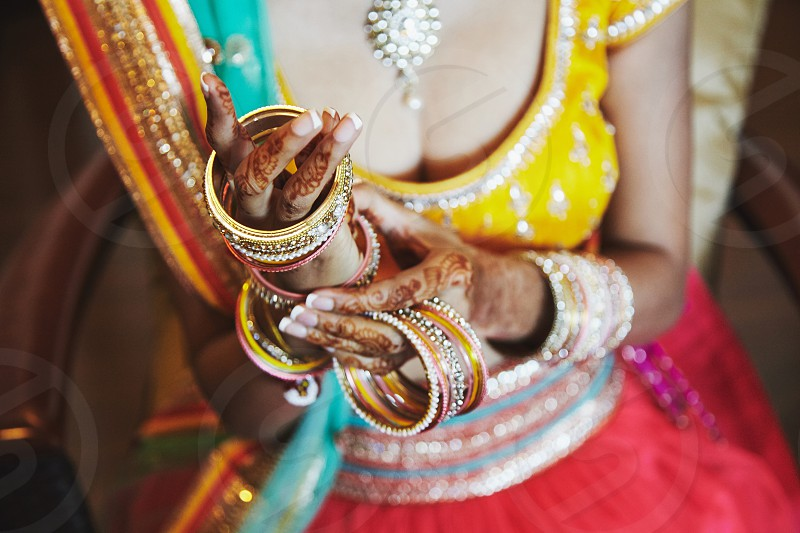 The close-up shot of Indian bride with beautiful saree in yellow blouse and red lehenga putting a lot of glitter bracelets (bangle) on hand with mehndi photo