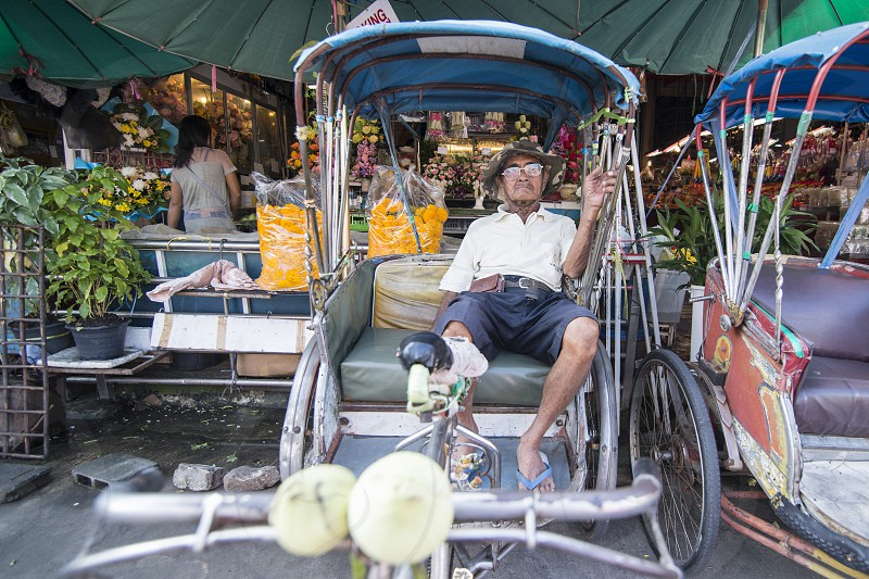 a bicycle ricksha at a road in the city centre of Khorat or Nakhon Ratchasima in Isan in Noertheast Thailand.  Thailand Khorat November 2017 photo