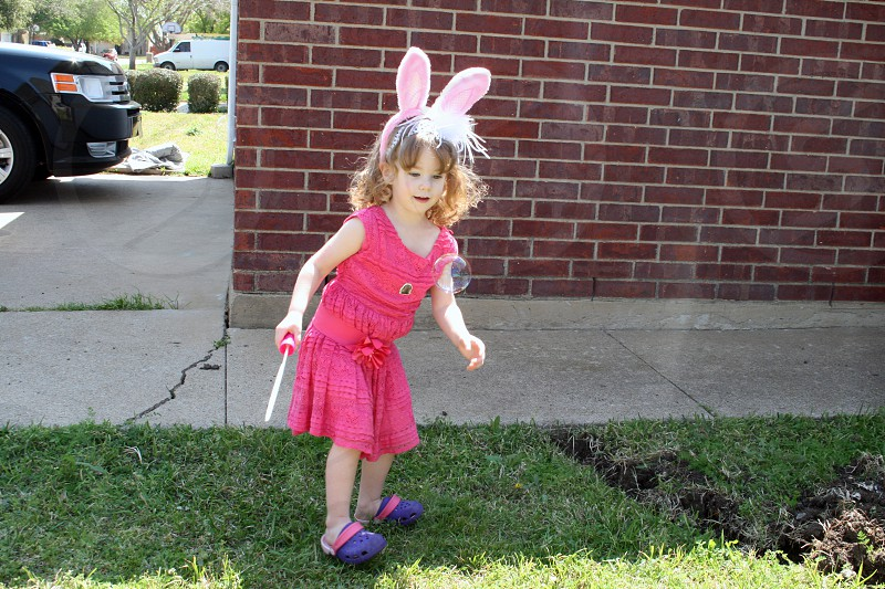 Young girl wearing bunny ears and watching a bubble with wonder and awe. photo