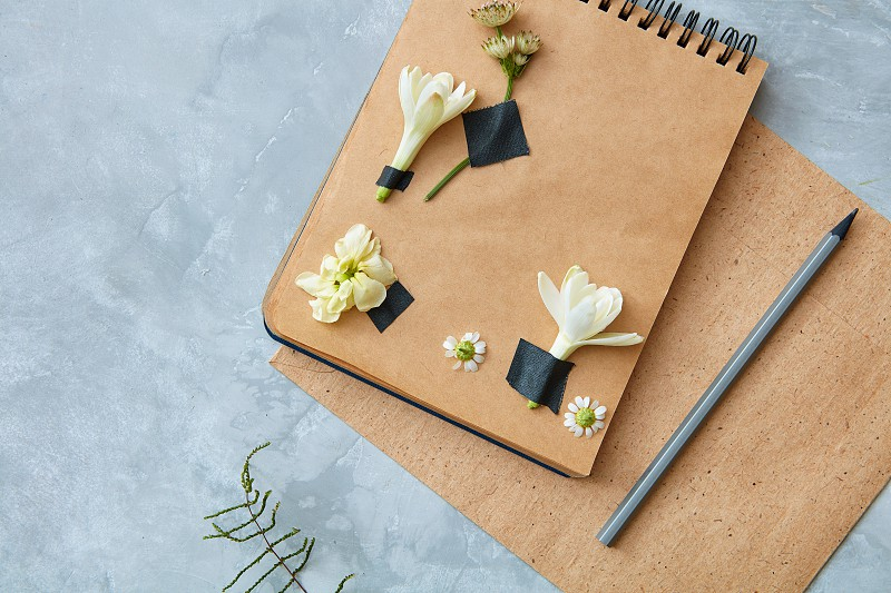 Top view of craft notebook with flower decoration with pencil on concrete background overhead view photo