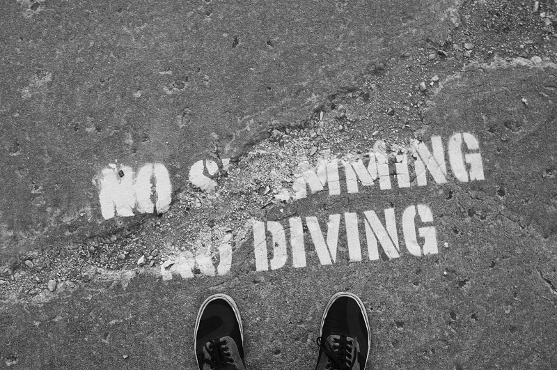 No Swimming No Diving signage painted on concrete ground photo