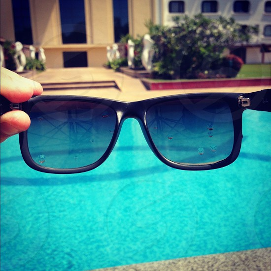 Sunglasses next to a swimming pool. Vacation holiday travel.  photo