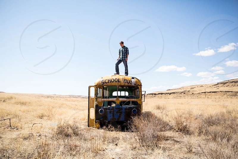 man in black and white checked dress shirt on top of yellow school bus photo