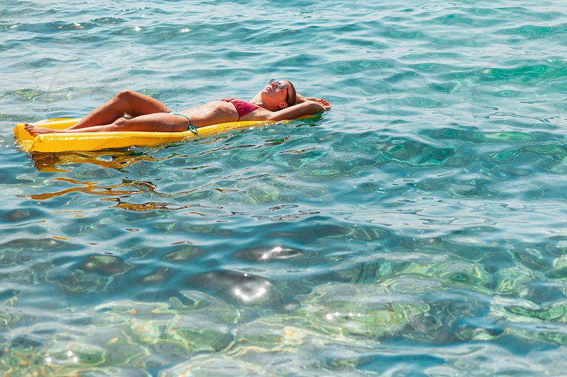 Young woman floating on the mattress in the sea photo