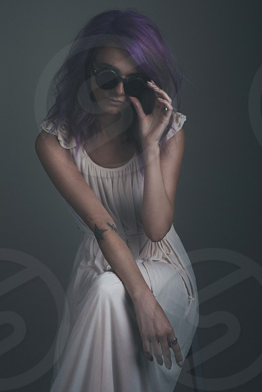 woman in cream drape maxi dress with cap sleeves and sunglasses on stool photo