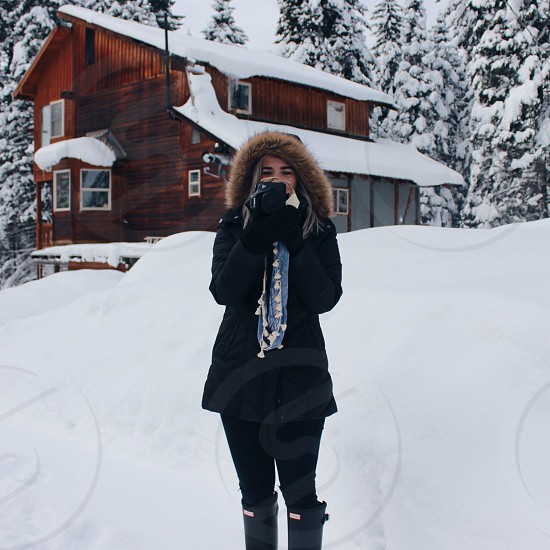 person in black and brown fur jacket standing on snow near brown wooden house photo